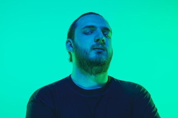 Retrato de un chico con luz de neón de colores en la pared verde. modelo masculino con estado de ánimo tranquilo y serio. expresión facial, estilo de vida y apariencia de los millenials. futuro, tecnologías.