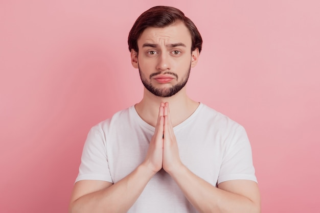 Retrato de chico nervioso molesto mantener las palmas juntas gritar pedir ayuda sobre fondo rosa