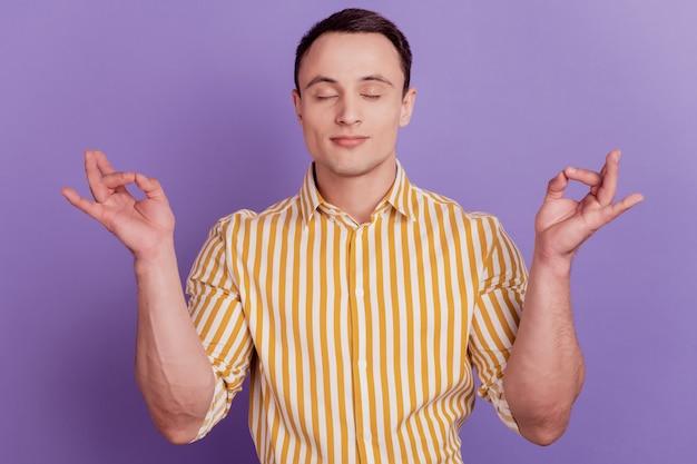 Retrato de chico relajado pacífico meditar ojos cerrados mantenga los dedos sobre fondo púrpura