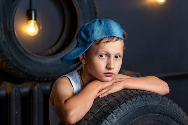 Retrato chico serio de 7 años de edad, apoyado en la llanta de un automóvil en el garaje