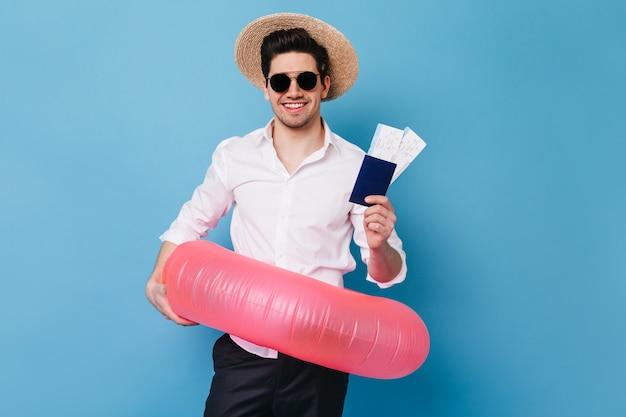 Retrato de chico con sombrero y gafas en el espacio azul. hombre de negocios en camisa tiene boletos para descanso, pasaporte y anillo de goma.