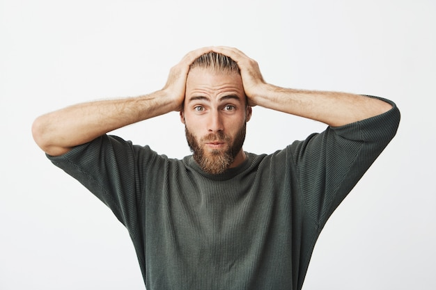 Retrato de chico sueco guapo con cabello moderno y barba se sorprendió