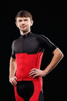 Retrato de un ciclista en ropa de entrenamiento sobre fondo negro