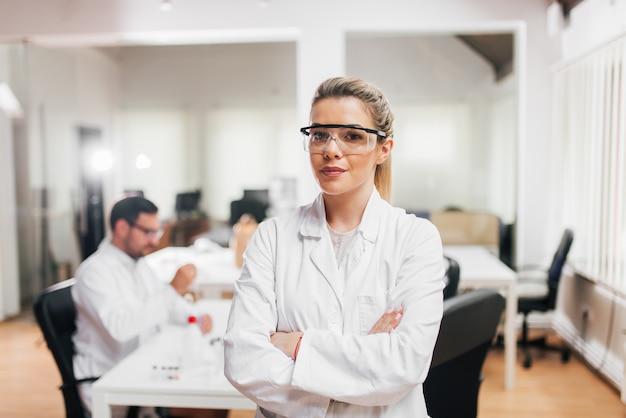 Retrato de una científica en ropa protectora para los ojos con los brazos cruzados. colegas en el fondo.
