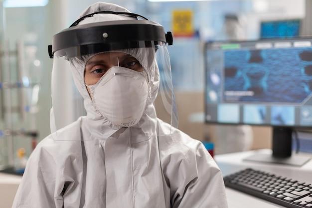 Retrato de científico cansado en mono mirando a la cámara sentado en un moderno laboratorio equipado