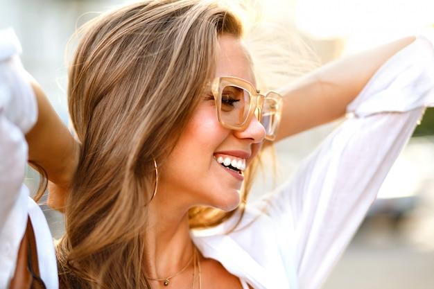 Retrato de cierre soleado positivo de alegre joven magnífica mujer blogger hipster