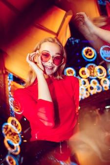 Retrato cinematográfico de la joven y bella mujer en la sala iluminada de neón con estilo músico