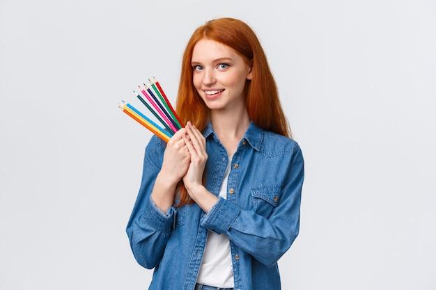 Retrato de cintura alta, soñadora y talentosa pelirroja guapa estudiante crea proyecto de diseño, dibuja arquitectura, sostiene lápices de colores y sonríe cámara feliz, blanco