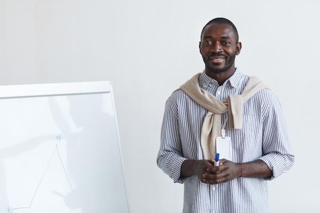 Retrato de cintura para arriba del entrenador de negocios afroamericano hablando con la audiencia en la conferencia o seminario educativo mientras está de pie junto a la pizarra y sonriendo, copie el espacio