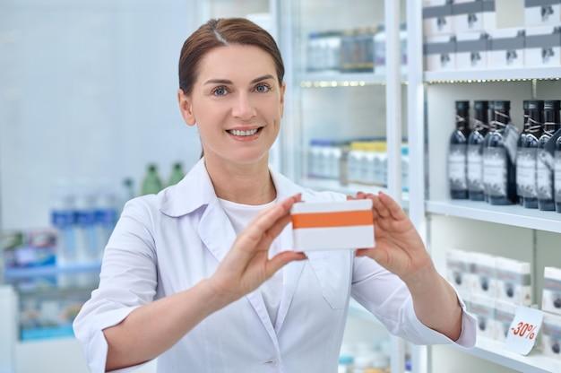 Retrato de cintura para arriba de un farmacéutico sonriente mostrando una caja de cartón con medicamentos ante la cámara