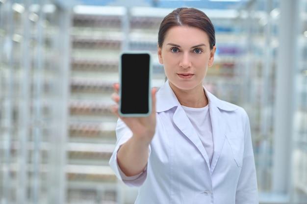 Retrato de cintura para arriba de un farmacéutico con una túnica blanca limpia que sostiene su teléfono inteligente frente a la cámara