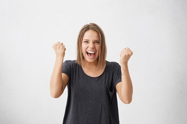 Retrato de cintura para arriba de la ganadora joven decidida y exitosa fuerte en camiseta casual levantando los brazos, apretando los puños, exclamando con alegría y emoción. concepto de victoria, éxito y logro