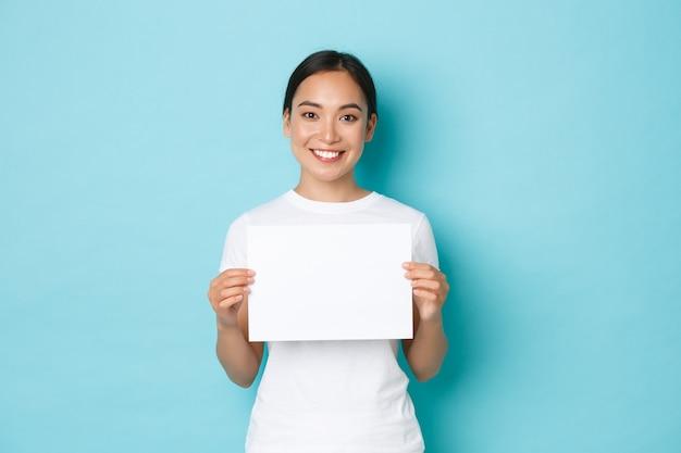 Retrato de cintura para arriba de una hermosa niña asiática sonriente buscando a alguien, haciendo un anuncio, sosteniendo un trozo de papel en blanco y mirando a cámara, de pie con un fondo azul claro.