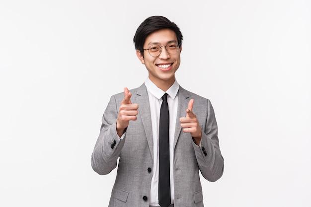 Retrato en la cintura del descarado y exitoso gerente de la oficina asiática joven en traje, empresario en busca de nuevos empleados, apuntando con las pistolas de los dedos como invitando a unirse al equipo, reclutar en la pared blanca