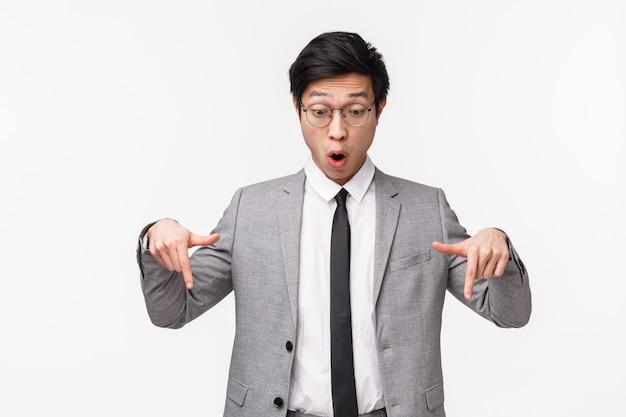 Retrato en la cintura del empresario asiático asustado e impresionado, gerente de la oficina viendo algo genial, descubre una gran oferta de descuento, usa traje gris, apuntando mirando hacia abajo en la pared blanca