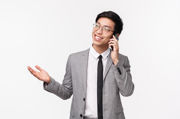 Retrato en la cintura del exitoso hombre de negocios asiático feliz y sonriente en traje gris, llamando a su compañero, hablando por teléfono, discutiendo negocios, explicando las oportunidades del cliente, gesticulando con la mano, en una pared blanca