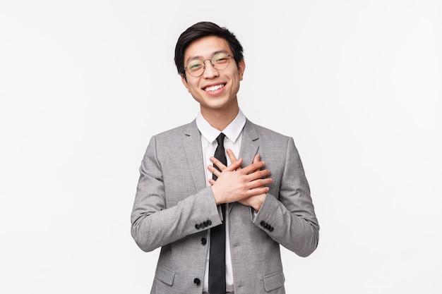 Retrato en la cintura del gerente de oficina masculino asiático joven agradecido y halagado, empresario de la mano y sonriendo, agradeciendo el cumplido, halagado y agradecido por las alabanzas, en una pared blanca