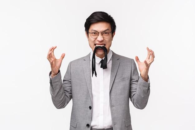 Retrato en la cintura del hombre asiático joven enojado, angustiado e irritado que come su propia corbata