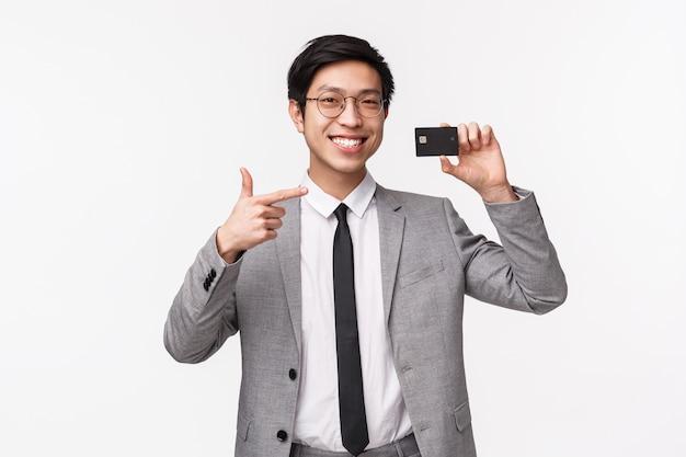 Retrato en la cintura del joven asiático satisfecho y apuesto con traje, mostrando tarjeta de crédito, señalando con una sonrisa de satisfacción, recomienda el uso de pagos no en efectivo, en una pared blanca