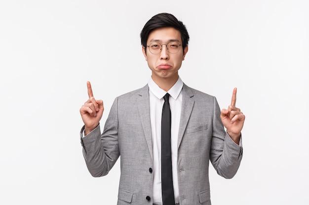 Retrato en la cintura del joven empleado de oficina asiático escéptico y sospechoso en traje gris, entrecerrando los ojos con incredulidad y haciendo una mueca sintiendo dudas sobre la persona que dice la verdad, apuntando con los dedos hacia arriba