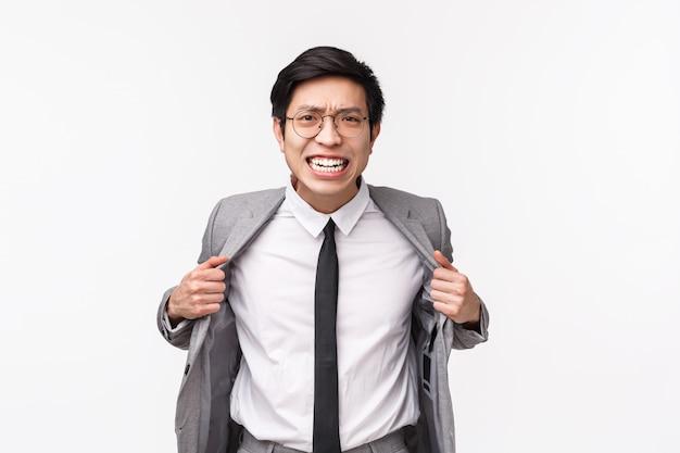 Retrato en la cintura de un joven empresario asiático agresivo y enojado con traje gris y corbata, rasgándose la ropa de ira, perdiendo la paciencia, angustiado de pie en la pared blanca