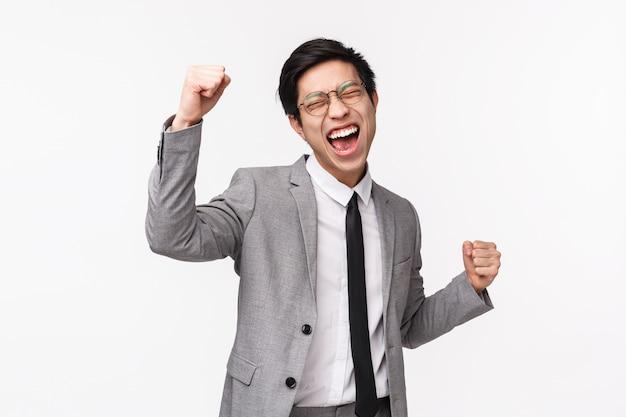 Retrato en la cintura del joven empresario asiático aliviado y exitoso, empresario masculino con traje gris, puño, bailar campeón, gritar sí victoria, triunfar sobre el logro, ganar