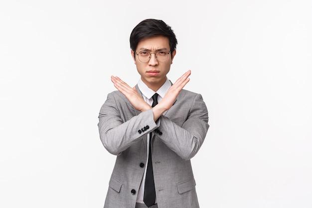 El retrato en la cintura del joven empresario asiático decidido de aspecto serio promete detener el acoso en su oficina, prohibir el mal comportamiento inapropiado, hacer gestos de prohibición cruzada