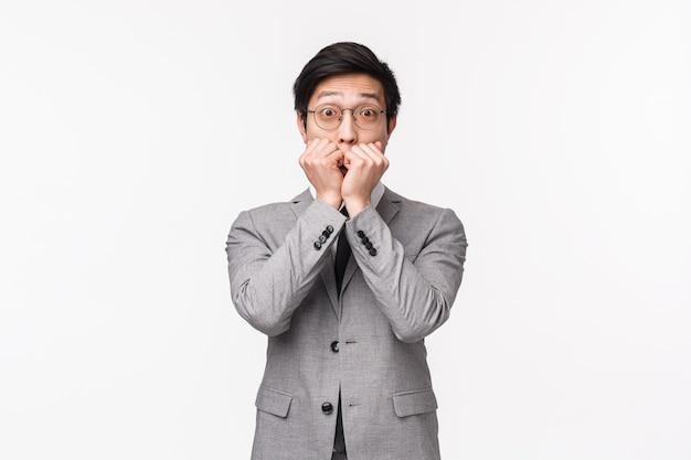Retrato en la cintura del joven empresario asiático guapo sorprendido e impresionado que cotillea con un compañero de trabajo, se sorprende al jadear, se tapa la boca y mira emocionado, en una pared blanca