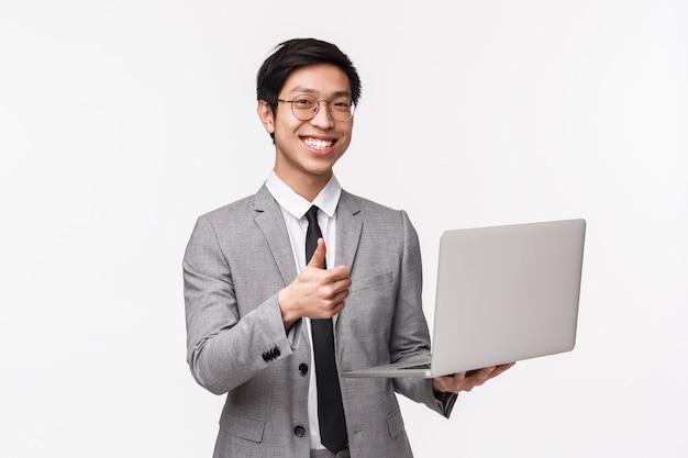 Retrato en la cintura del joven empresario asiático satisfecho, feliz y complacido, programador de ti en traje, presenta su nuevo proyecto, muestra su aprobación con el pulgar hacia arriba y sostiene la computadora portátil, en una pared blanca