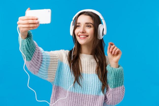 Retrato en la cintura linda mujer bastante joven con cabello largo y oscuro, sonrisa alegre, usar auriculares, tomar selfie en teléfono inteligente, levantar la mano con el teléfono y posar, de pie azul