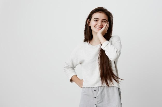 Retrato en la cintura de la modelo femenina morena sonriendo alegremente con dientes blancos, contento de recibir buenas noticias o presentes. la mujer emocionada expresa emotinos positivos, sostiene la mano en la mejilla con asombro.