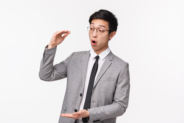 Retrato en la cintura de un oficinista asiático guapo y entusiasmado que le dice al cliente sobre grandes oportunidades de ingresos, describe el proyecto que da forma al gran objeto, una gran suma de dinero, se ve sorprendido