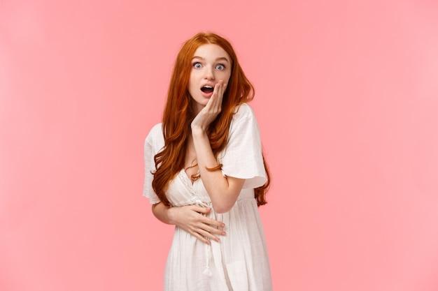 Retrato en la cintura sorprendida y curiosa, la niña pelirroja asombrada escuchó noticias increíbles, cotilleando con la novia en la fiesta, con la boca abierta impresionada, la mejilla al tacto se veía maravillada, pared rosa