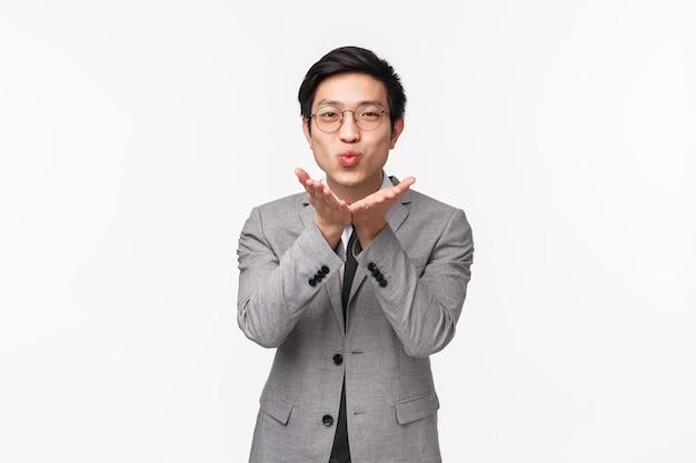 Retrato a la cintura de un tonto novio asiático romántico y guapo, hombre de negocios en traje gris, tomados de la mano cerca de los labios doblados para enviar un beso al aire, sonriendo lindo, de pie en la pared blanca