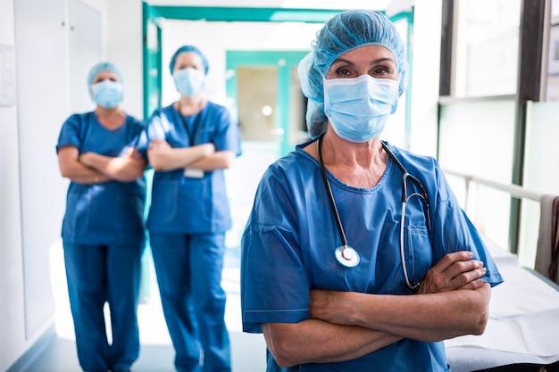 Retrato de cirujano y enfermeras de pie con los brazos cruzados