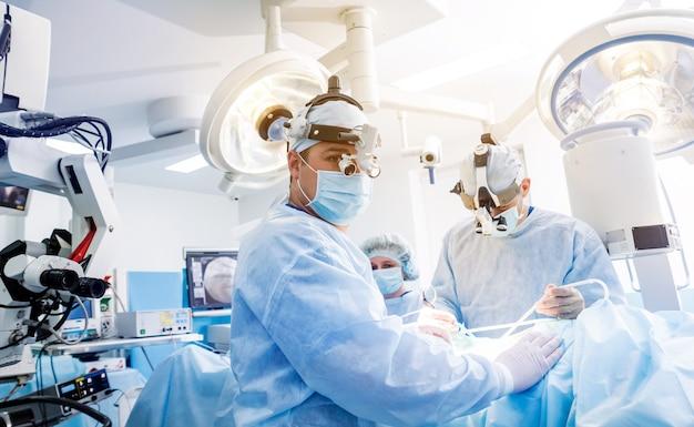 Retrato de cirujano espinal en quirófano con equipo de cirugía.