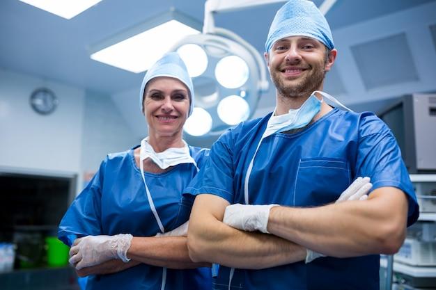 Retrato de cirujanos de pie con los brazos cruzados en la sala de operación