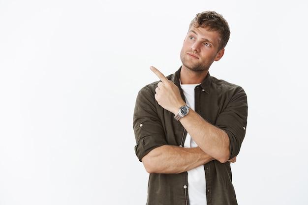 Retrato de cliente masculino guapo impresionado haciendo compras tlting cabeza con curiosidad mientras apunta y mira a la izquierda con interés al ver algo genial, posando sobre una pared gris