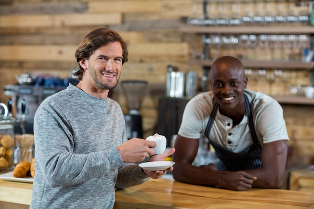 Retrato de un cliente masculino sonriendo mientras toma un café