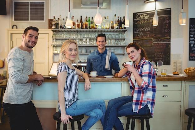 Retrato de clientes felices y camarero en coffee house