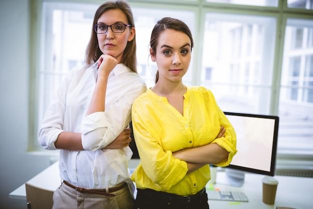 Retrato de colegas confiados de pie con los brazos cruzados en la oficina
