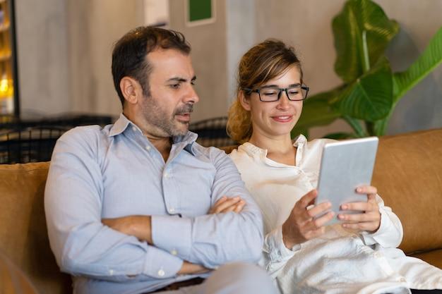 Retrato de colegas felices que usan la tableta de la pc en el vestíbulo en el descanso