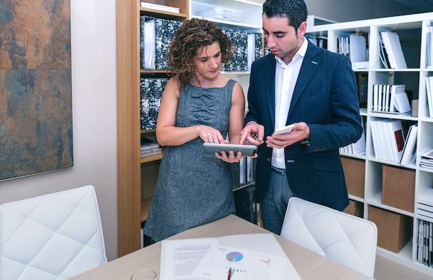 Retrato de colegas que buscan documento en tableta electrónica en una reunión de negocios