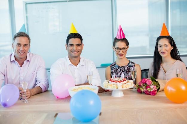 Retrato de colegas sonrientes celebrando el cumpleaños de la mujer