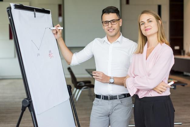 Retrato de los colegas sonrientes del negocio que dibujan plan en rotafolio.