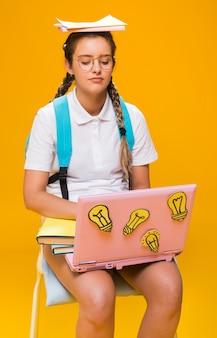 Retrato de colegiada estudiando con portátil