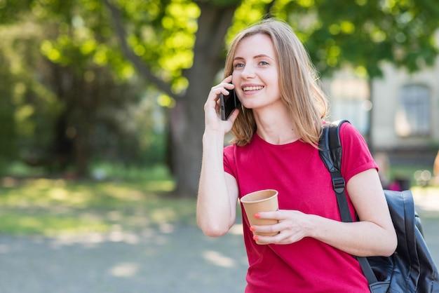 Retrato de colegiada haciendo llamada en el parque