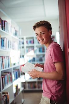 Retrato de colegial feliz sosteniendo el libro en la biblioteca