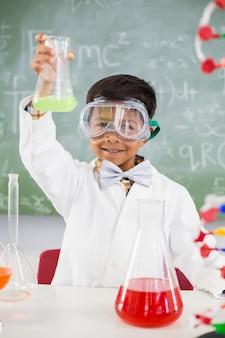 Retrato de colegial haciendo un experimento químico en laboratorio