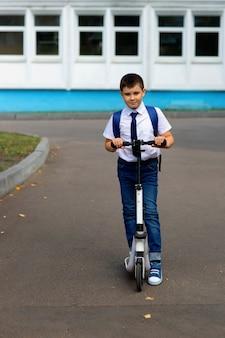 Retrato de un colegial joven y elegante con una camisa blanca, corbata azul y una mochila
